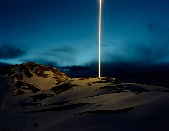 beams of light illuminate the snowy landscape by kevin cooley